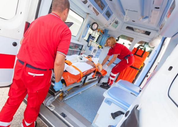 ratownicy wkładają chorego do karetki